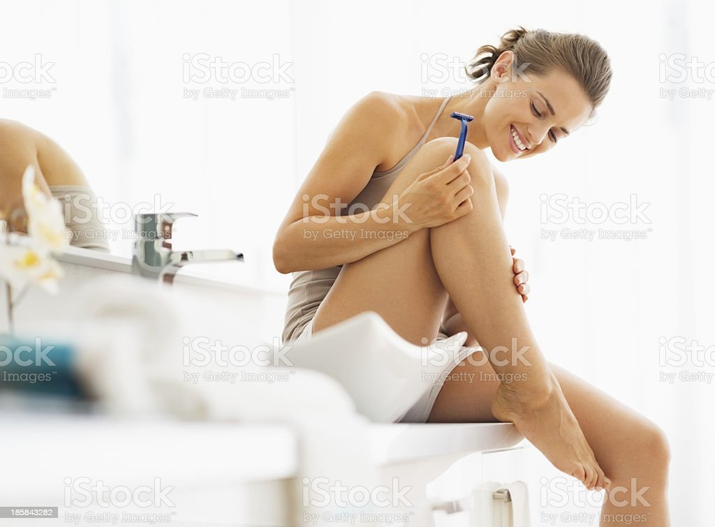 Happy woman checking legs after shaving stock photo