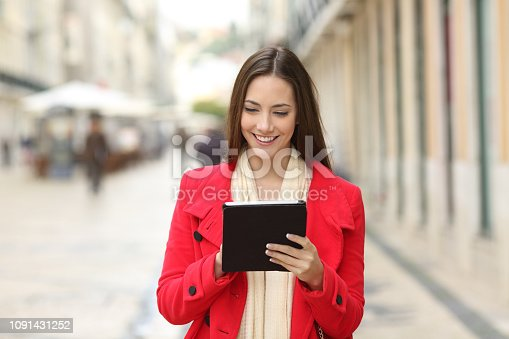 istock Happy woman checking tablet content in the street 1091431252