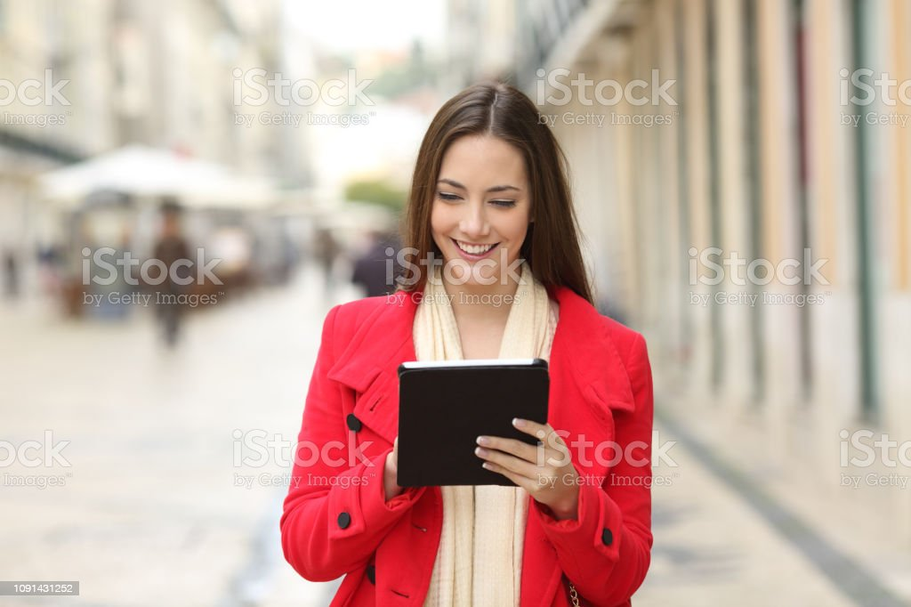 Happy woman checking tablet content in the street stock photo
