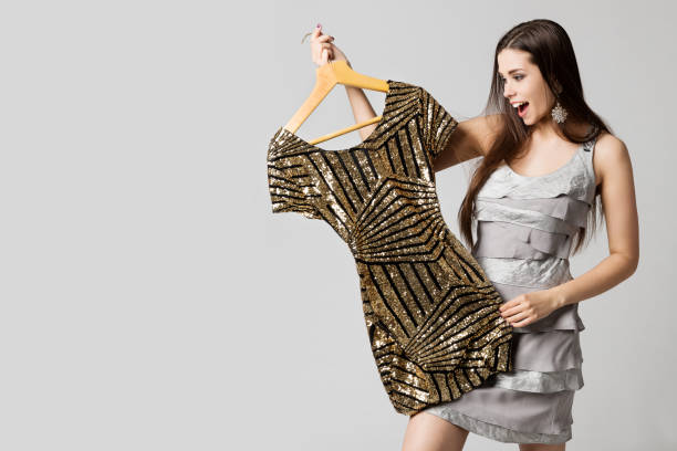 Happy Woman Choosing Dress, Attractive Girl Holding Gold Clothes on Hanger over White stock photo