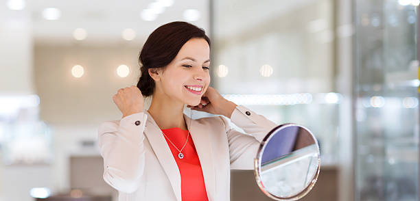 glückliche frau wählen sie anhänger im juweliergeschäft - diamanten kaufen stock-fotos und bilder