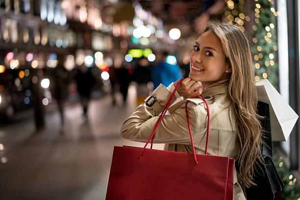 glückliche frau weihnachts-shopping - günstige weihnachtsgeschenke stock-fotos und bilder