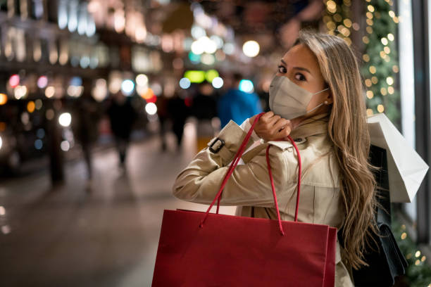 Happy woman Christmas shopping wearing a facemask Happy woman Christmas shopping and wearing a facemask while carrying bags – COVID-19 pandemic concepts cheap stock pictures, royalty-free photos & images