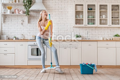 1081403344 istock photo Happy woman cleaning home and having fun by singing at mop like in microphone 1190252839