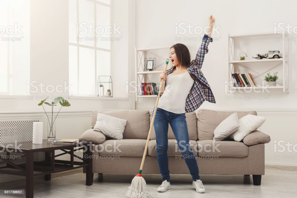 愉快的婦女清潔家與拖把和樂趣 - 免版稅一個人圖庫照片