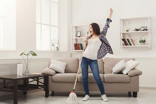 愉快的婦女清潔家與拖把和樂趣 照片檔及更多 一個人 照片