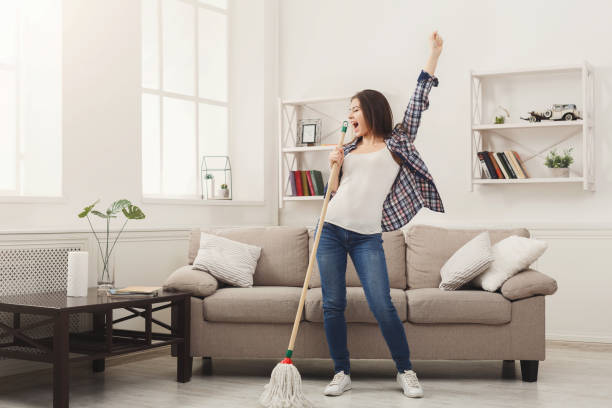 Happy woman cleaning home with mop and having fun Happy woman cleaning home, singing at mop like at microphone and having fun, copy space. Housework, chores concept cleaning equipment stock pictures, royalty-free photos & images