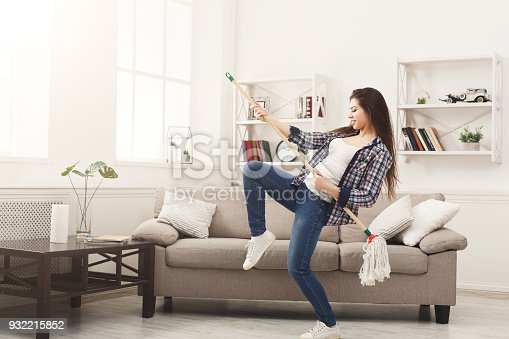 1081403344 istock photo Happy woman cleaning home with mop and having fun 932215852