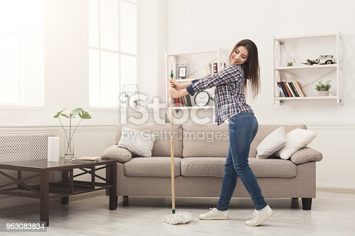 1081403344 istock photo Happy woman cleaning home with mop and having fun 953083834