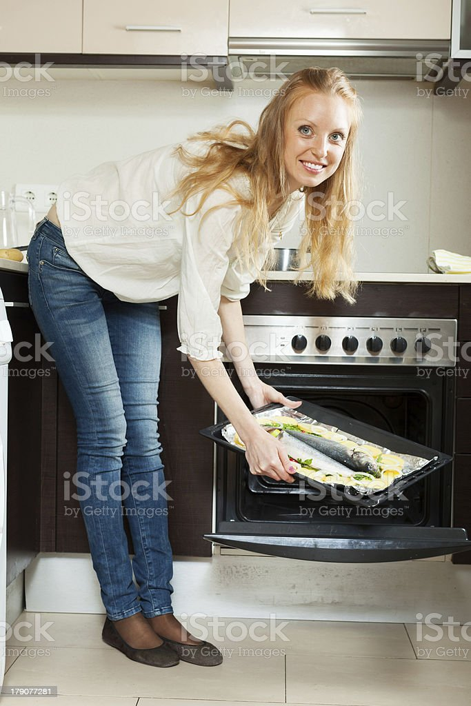 Happy woman cooking fish in oven stock photo