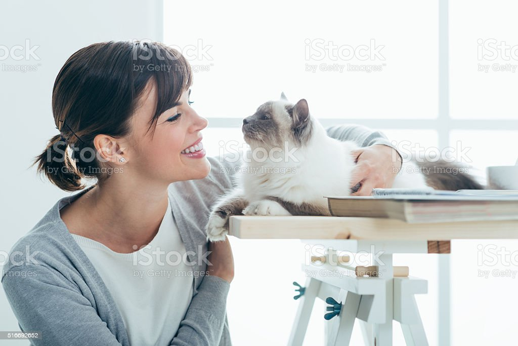Happy woman cuddling her cat stock photo