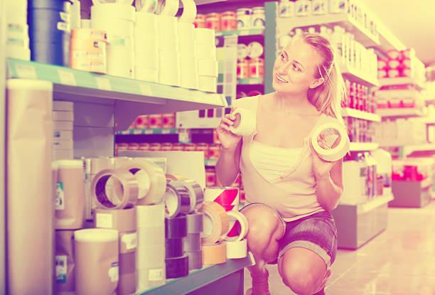 happy woman customer choosing adhesive tape in household store - papierrollenhalter stock-fotos und bilder