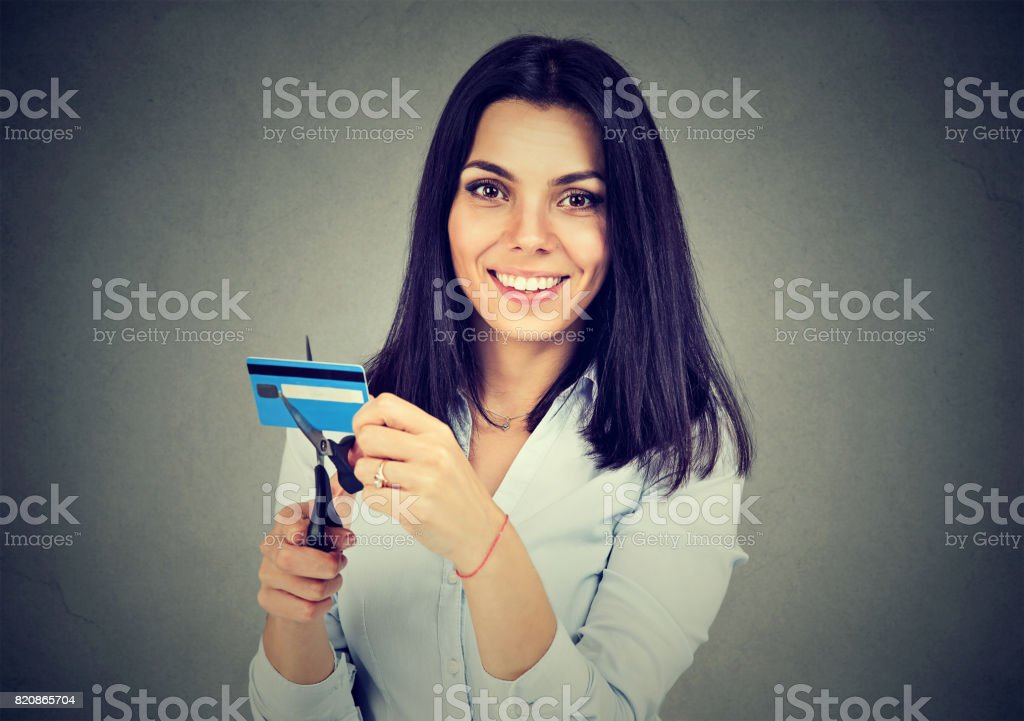 Happy woman cutting in half her credit card with scissors isolated on gray background stock photo