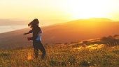 istock Happy woman  dances, jump, rejoices, laughs  on sunset in nature 840264768