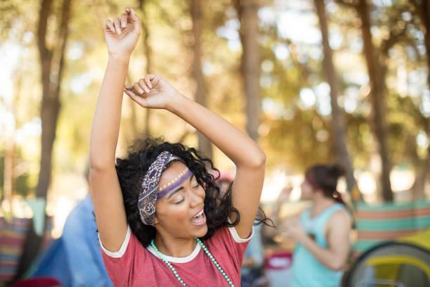 glückliche frau tanzt auf campingplatz - tanz camp stock-fotos und bilder
