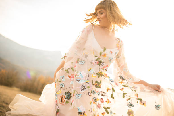 glückliche frau tanzt in einem blumigen weißen kleid - hippie kleider stock-fotos und bilder