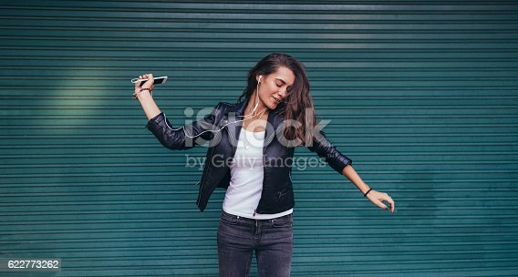 istock Happy woman dancing to the music 622773262