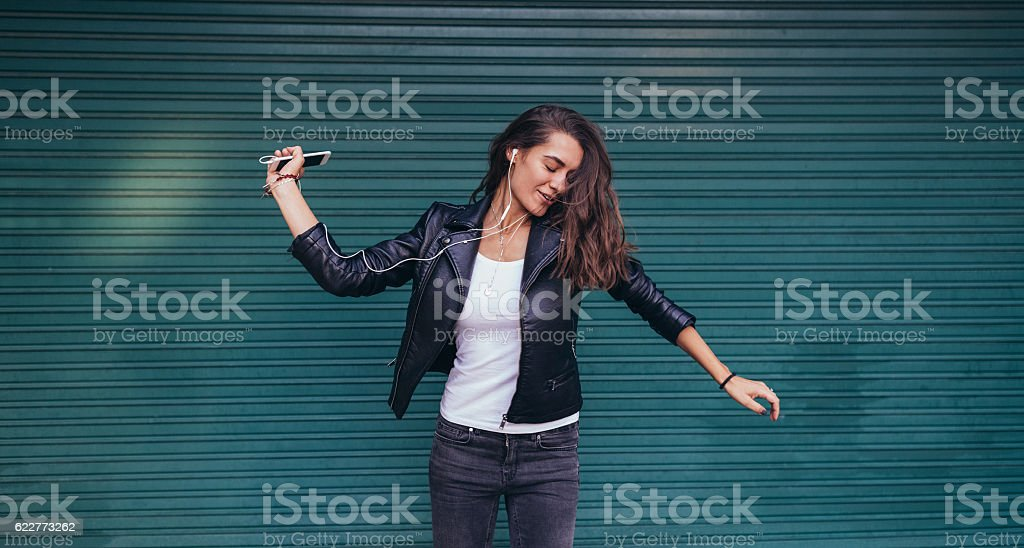 Happy woman dancing to the music stock photo