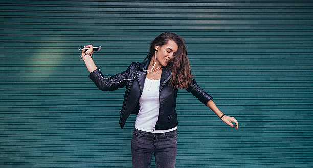 happy woman dancing to the music - lederjacke frauen stock-fotos und bilder
