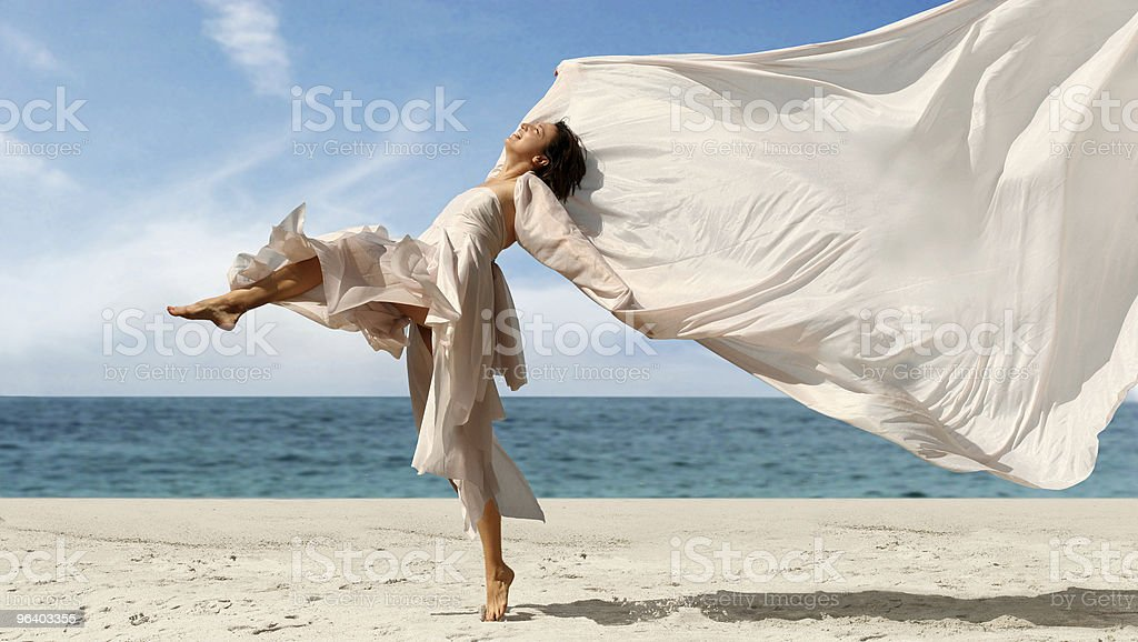 Happy woman dancing with blowing fabric on the beach - Royalty-free 20-29 Years Stock Photo