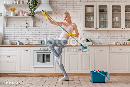 1081403344 istock photo Happy woman dancing with mop and having fun while cleaning home 1190252816