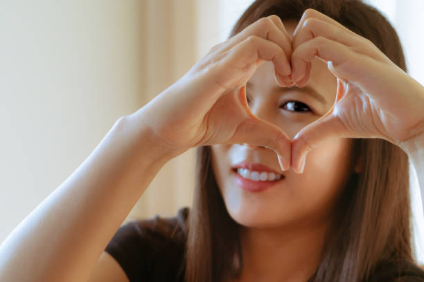 Happy Woman Day. Beautiful Happy Woman Holding Heart Shaped Hands. Healthy Eyes And Vision. stock photo