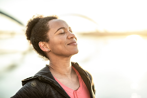 Sporty African American woman enjoying sunlight and day dreaming.