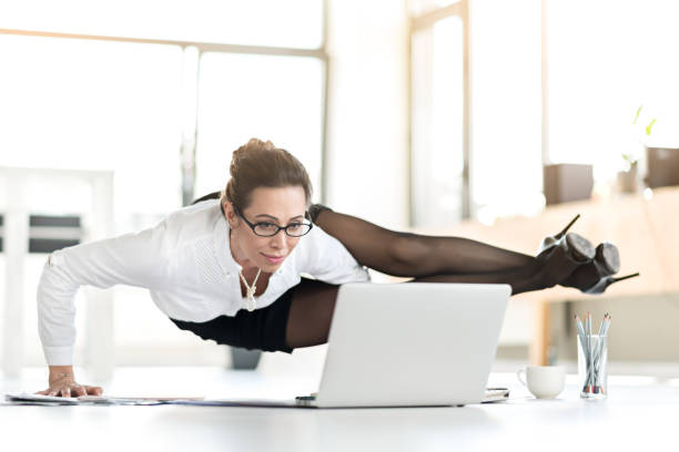 Happy woman doing exercises during working day stock photo