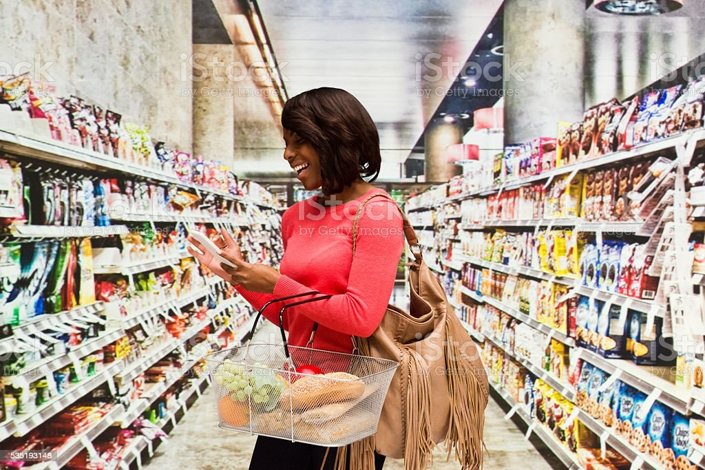 Happy woman doing grocery shopping stock photo