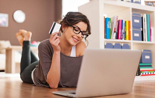 glückliche frau machen online-shopping zu hause - sofa online kaufen stock-fotos und bilder