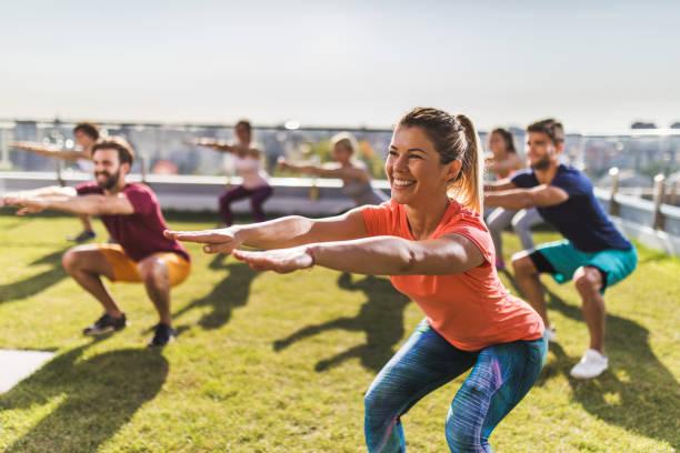 mujer feliz haciendo sentadillas durante un deportivo entrenamiento con sus amigos. - aeróbic fotografías e imágenes de stock