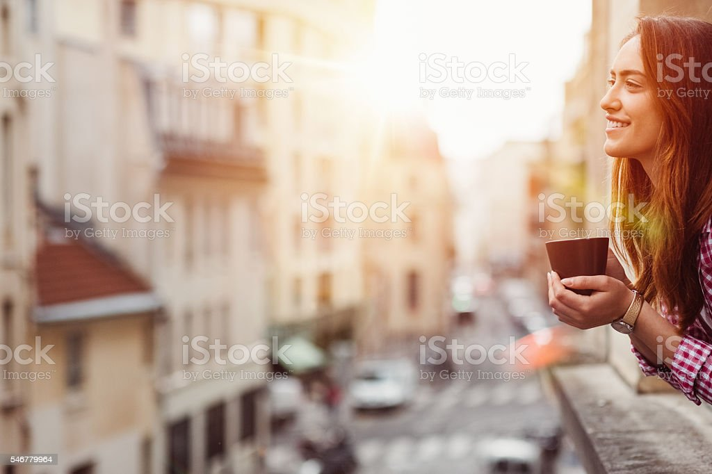 Happy woman drinking coffee at the window stock photo