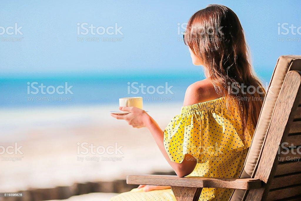 Happy woman drinking coffee cappuccino enjoying beach view stock photo