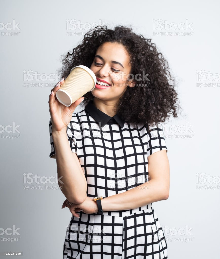 Happy woman drinking coffee Portrait of beautiful young woman drinking coffee from disposable cup against gray background 20-24 Years Stock Photo