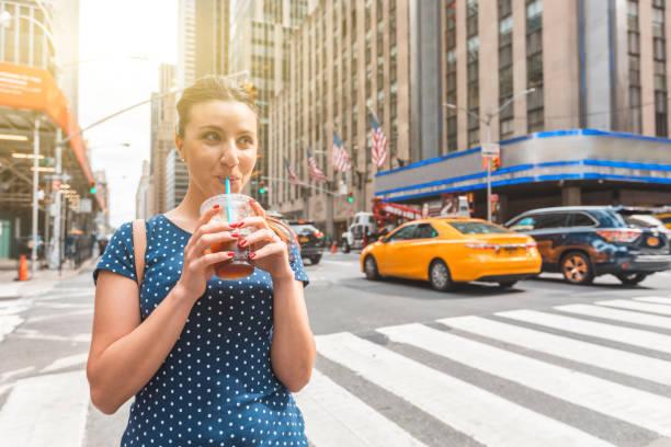 wanita bahagia minum es kopi di new york - traveler new york potret stok, foto, & gambar bebas royalti