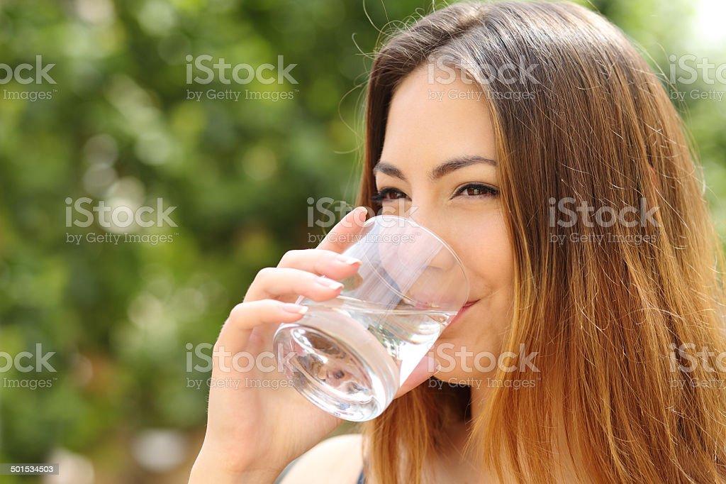 Glückliche Frau trinkt Wasser aus Glas im Freien – Foto