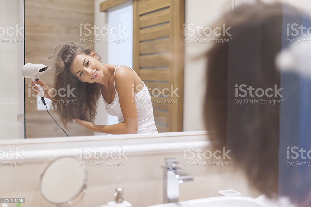 Happy woman drying her hair in bathroom. stock photo