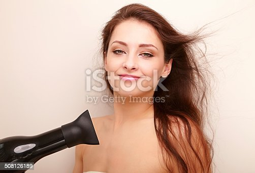 639833996istockphoto Happy woman drying long brown hair and looking 508126189