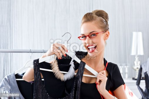 Happy young adult woman shopping in luxury boutique, showing black dress to the camera.