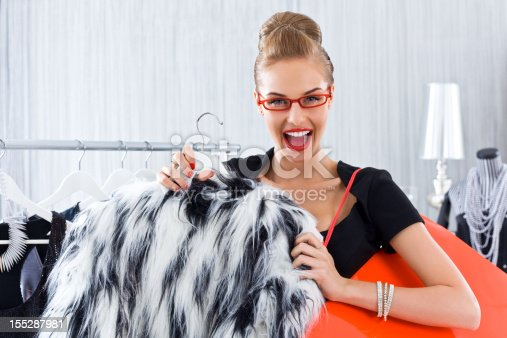 Happy young adult woman shopping in luxury boutique, reacting on special price of fur jacket.