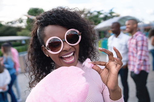 Portrait of a happy woman eating a cotton candy at an amusement park and wearing fun glasses - lifestyle concepts