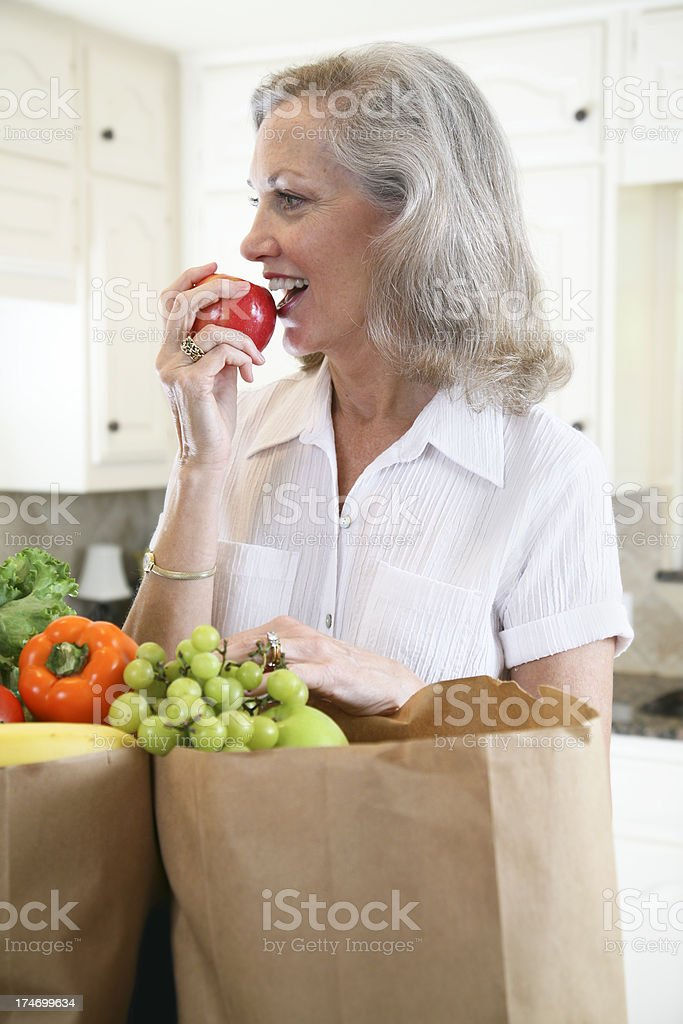 Happy Woman Eating an Apple in Her Kitchen royalty-free stock photo