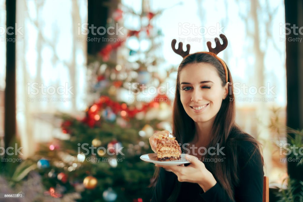 Happy Woman Eating Cake at Christmas Dinner Party stock photo