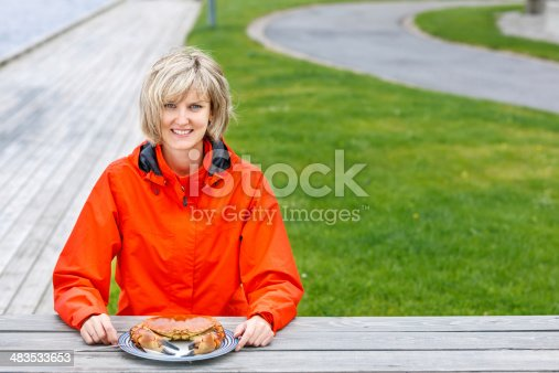 Happy woman eating crab outdoors