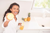 Smiling young woman showing a slice of pineapple and a jar with freshly squeezed sweet ananas juice.