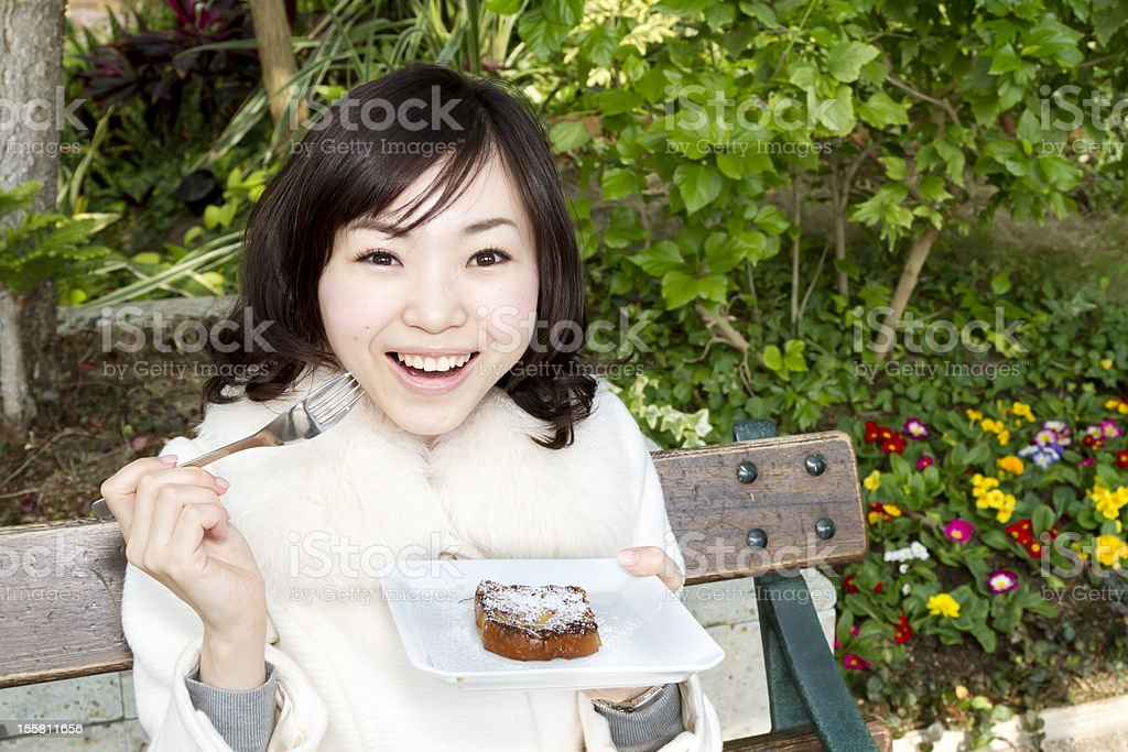 Happy Woman Eating French Toast in Park royalty-free stock photo