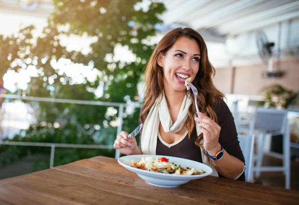 Happy woman eating fresh salad at restaurant stock photo