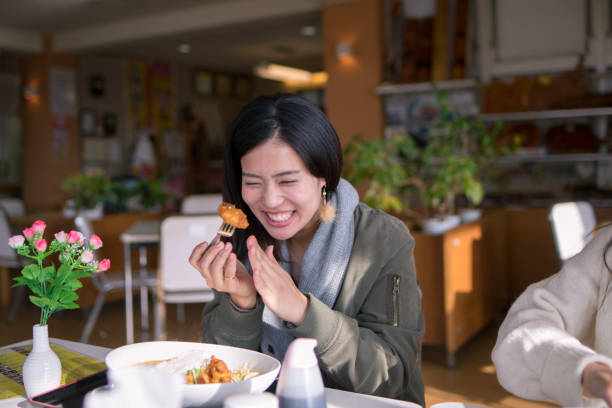 Happy woman eating fried chicken for lunch stock photo