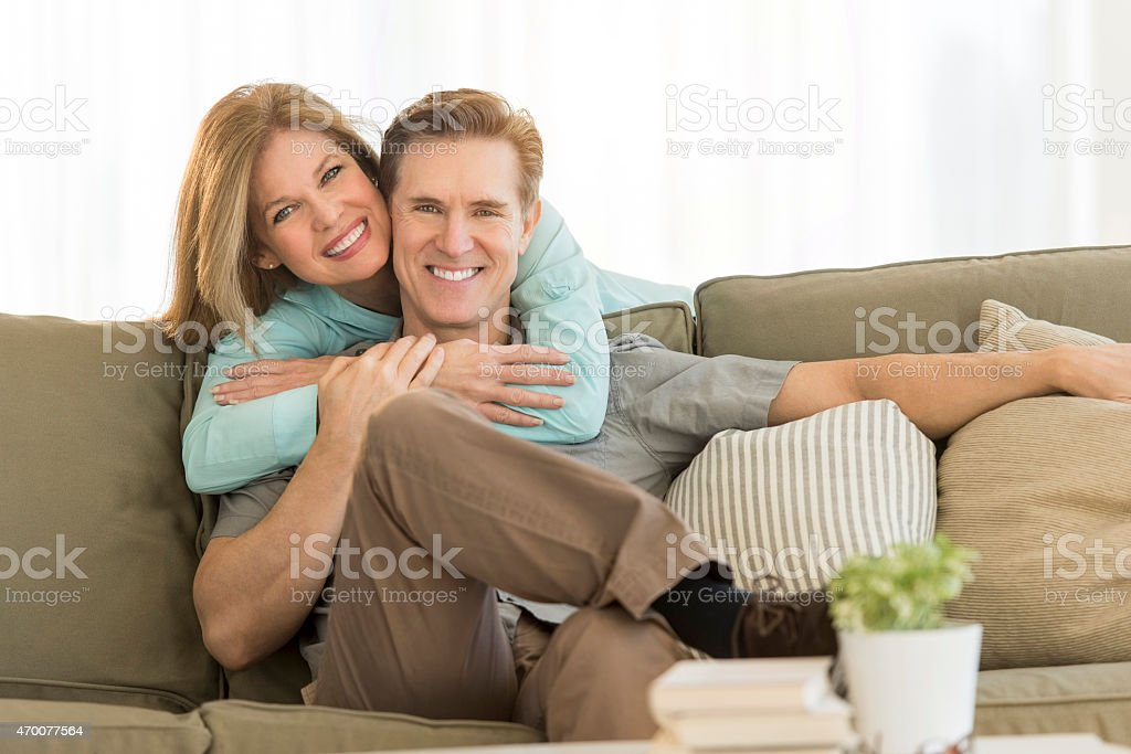 Happy woman embracing man on sofa at home stock photo
