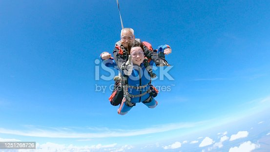 A woman is enjoying her first parachute jump. She jumped with an experienced skydiving instructor. The parachuting instructor shows the class with his thumb up.